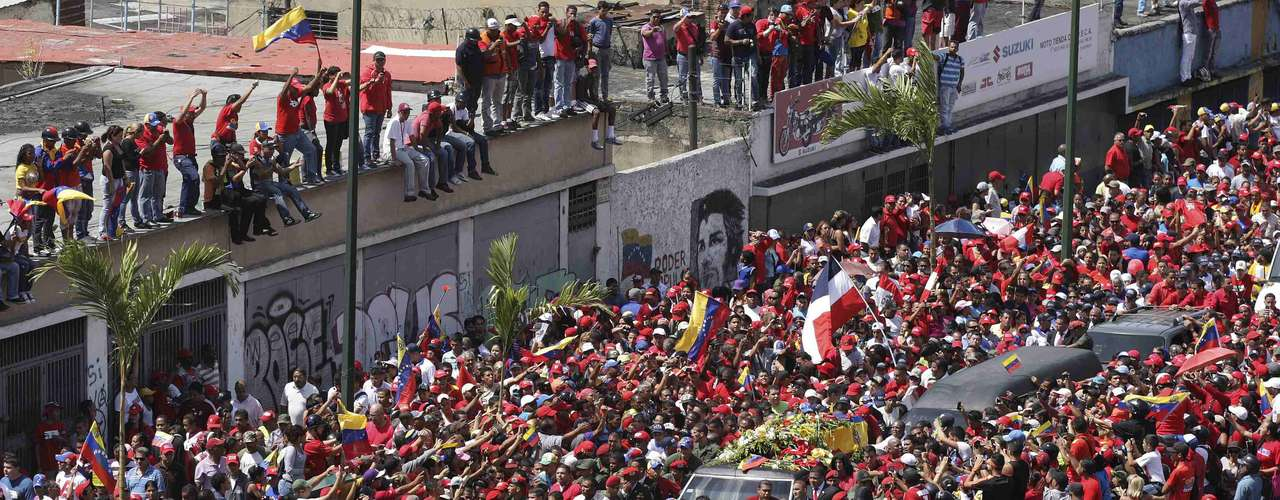 The coffin of Venezuela's late President Hugo Chavez is driven through the streets of Caracas after leaving the military hospital where he died of cancer, in Caracas, March 6, 2013. Authorities have not yet said where Chavez will be buried after his state funeral on Friday.REUTERS/Christian Veron (VENEZUELA - Tags: POLITICS OBITUARY)