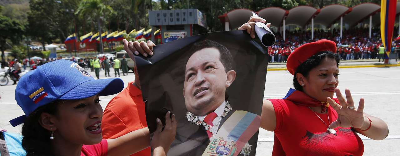 Supporters of Venezuela's late President Hugo Chavez carry a portrait of him as they wait for his coffin to arrive at the Military Academy in Caracas, March 6, 2013. Authorities have not yet said where Chavez will be buried after his state funeral on Friday. REUTERS/Jorge Silva (VENEZUELA - Tags: POLITICS OBITUARY)