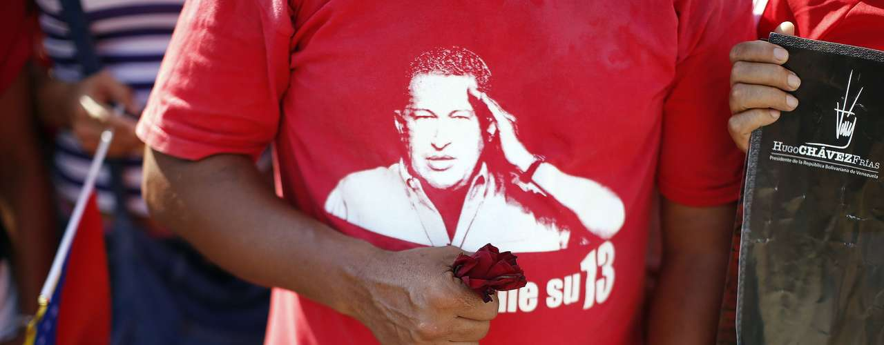 A supporter of late Venezuelan leader Hugo Chavez holds a flower as Chavez's coffin arrives at the Military Academy, where his wake will be held, in Caracas March 6, 2013. Authorities have not yet said where Chavez's remains will be buried after his state funeral on Friday.      REUTERS/Jorge Silva (VENEZUELA - Tags: POLITICS OBITUARY)