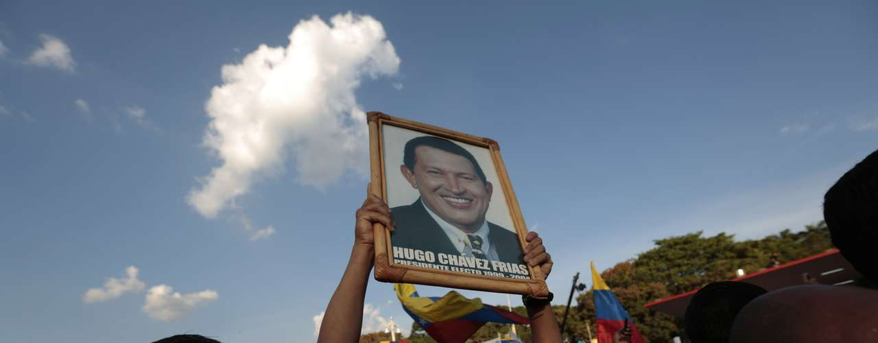 A supporter of the late Venezuelan President Hugo Chavez  holds a portrait of Chavez while waiting at the street as his coffin is driven through the streets of Caracas, March 6, 2013. Authorities have not yet said where Chavez will be buried after his state funeral on Friday. REUTERS/Jorge Dan Lopez (VENEZUELA - Tags: OBITUARY POLITICS)
