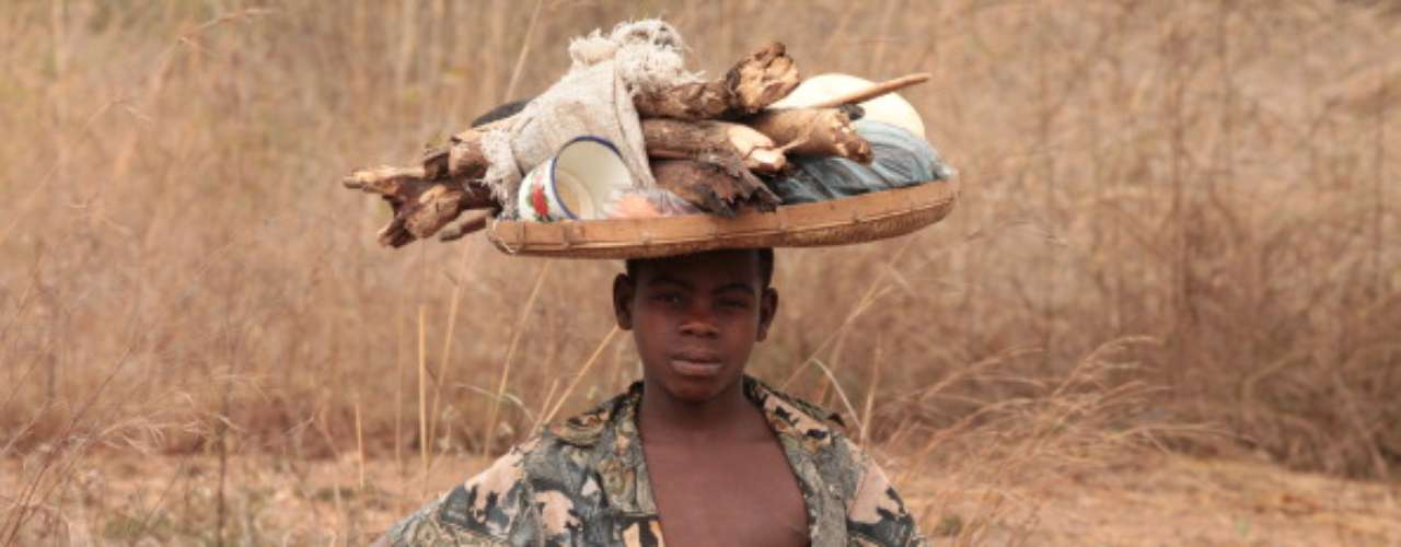 Mozambique está entre los últimos tres menos privilegiados. En la gráfica vemos a un niño que carga madera para poder comer algo en casa.