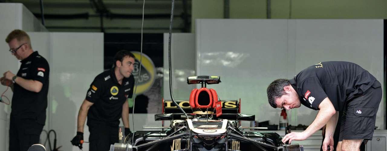 Los mecánicos de Lotus revisan el auto de Romain Grosjean a unos minutos de arrancar las prácticas en el circuito de Sepang.