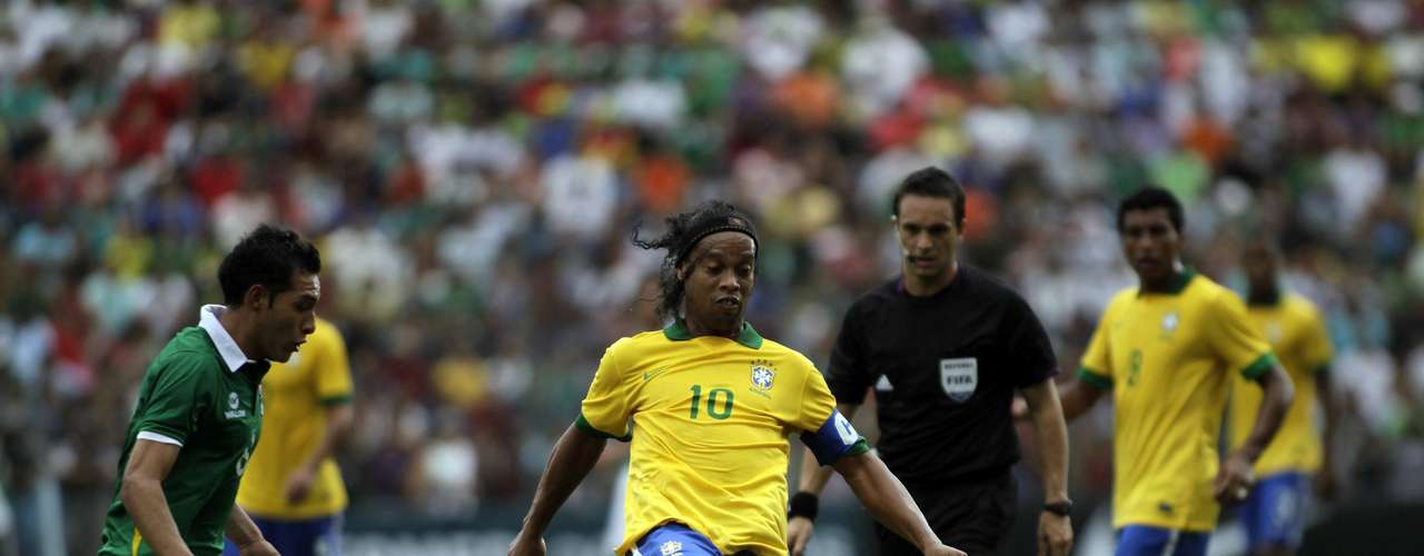 Ronaldinho (C) of Brazil controls the ball against Bolivia's Walter Veizaga (L) during a international friendly soccer match at Ramon Tauchi Aguilera Stadium in Santa Cruz April 6, 2013.