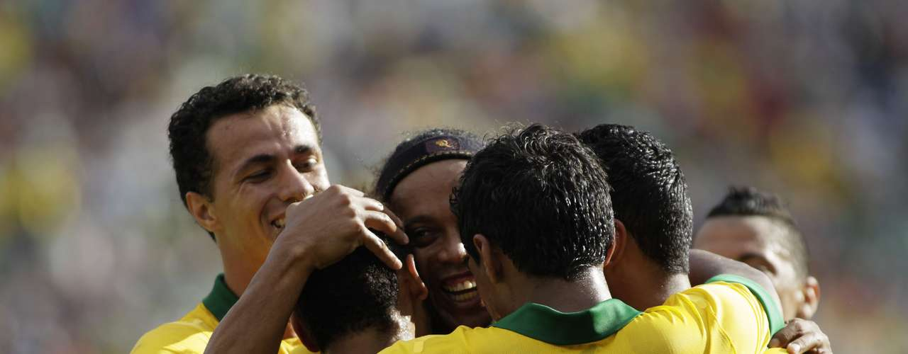Brazil's Ronaldinho (C) congratulates Neymar (2L) as teammates embrace him after scoring a goal against Bolivia during a international friendly soccer match at Ramon Tauchi Aguilera Stadium.