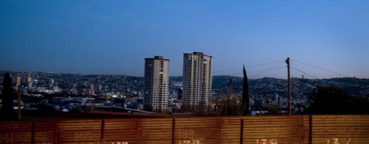 Desde la despoblada colina estadounidense, en una carretera que corre a lo largo de la valla divisoria, se escucha el canto de los gallos mexicanos. Al fondo se ven las casas humildes del barrio tijuanense Colonia Libertad, apretujadas contra la valla que usan para ahorrarse una pared.