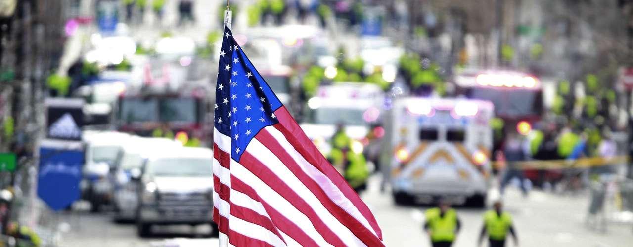 Una bandera estadounidense ondea mientras trabajadores médicos socorren a los heridos tras las explosiones. En el maratón participaban más de 26 mil corredores de todo el mundo.