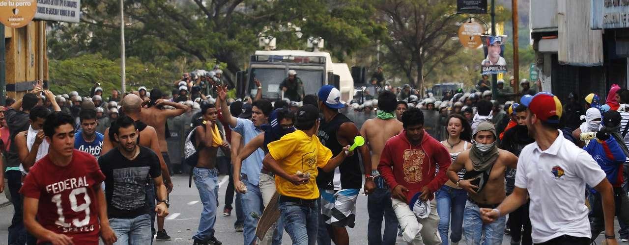 Los jóvenes, algunos con el rostro cubierto con camisetas para protegerse de los gases lacrimógenos, se replegaron hacia una de las avenidas de la urbanización Altamira, en el este de la ciudad, donde formaron una barricada con restos de basura que luego incendiaron.