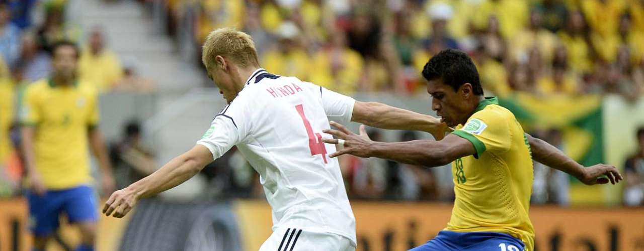 El centrocampista Paulinho intenta robarle el balón al delantero Keisuke Honda.