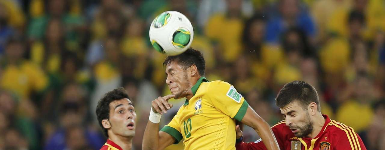 Brazil's Neymar (C) heads the ball between Spain's Alvaro Arbeloa (L) and Gerard Pique during the Confederations Cup final soccer match at the Estadio Maracana in Rio de Janeiro June 30, 2013. REUTERS/Sergio Moraes (BRAZIL  - Tags: SPORT SOCCER)