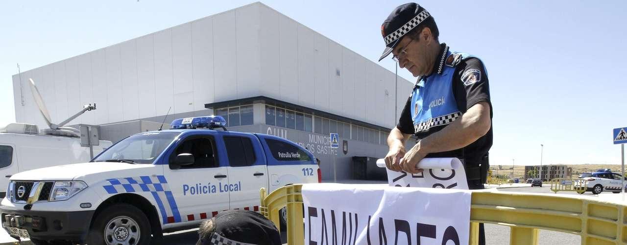 Agentes de la Policía Local colocan un cartel a la entrada del polideportivo municipal \
