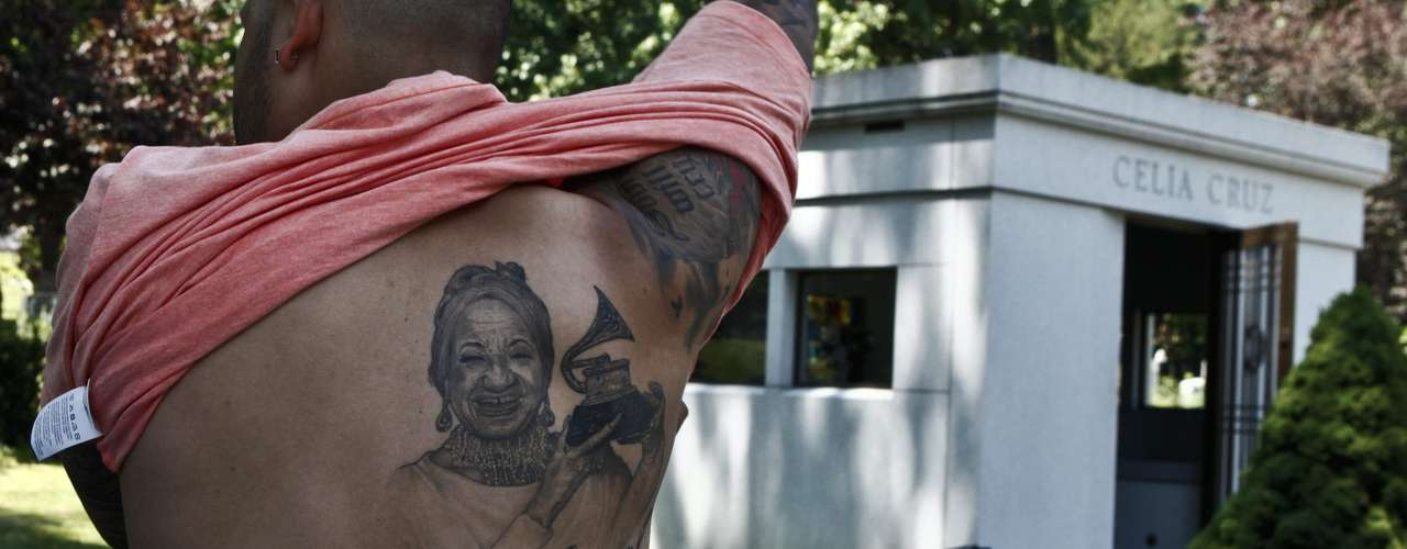 Un hombre exhibe un tatuaje de Celia Cruz frente al mausoleo de la artista en el cementerio Woodlawn en el Bronx, Nueva York (EE.UU.), durante la conmemoración del décimo aniversario de la muerte de la artista cubana. Sus fanáticos rindieron tributo a su reina con flores, música y bailes en su última morada, donde descansa junto a su inseparable Pedro Knight.