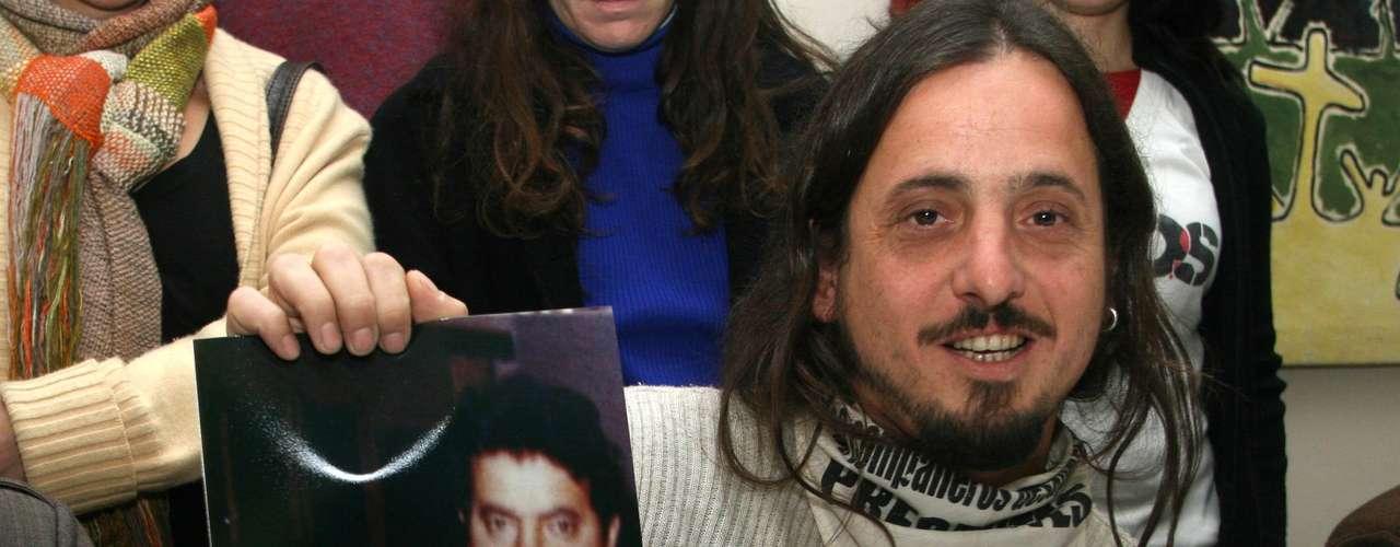 Emilio Goya exhibe una foto de sus padres detenidos-desaparecidos, con su hermano en brazos. Fue recuperado como el nieto 92 por las abuelas de Plaza de Mayo.