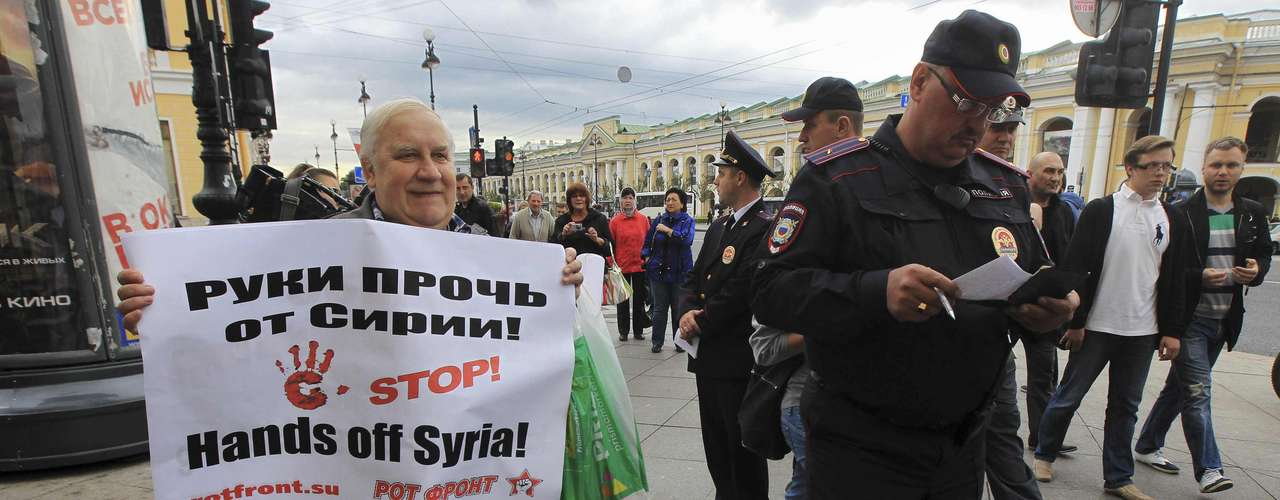A man holds a placard protesting against a possible military operation in Syria as he stages a one-person piquet on the first day of the G20 Summit in central St. Petersburg September 5, 2013. REUTERS/Stringer (RUSSIA - Tags: POLITICS BUSINESS CIVIL UNREST)