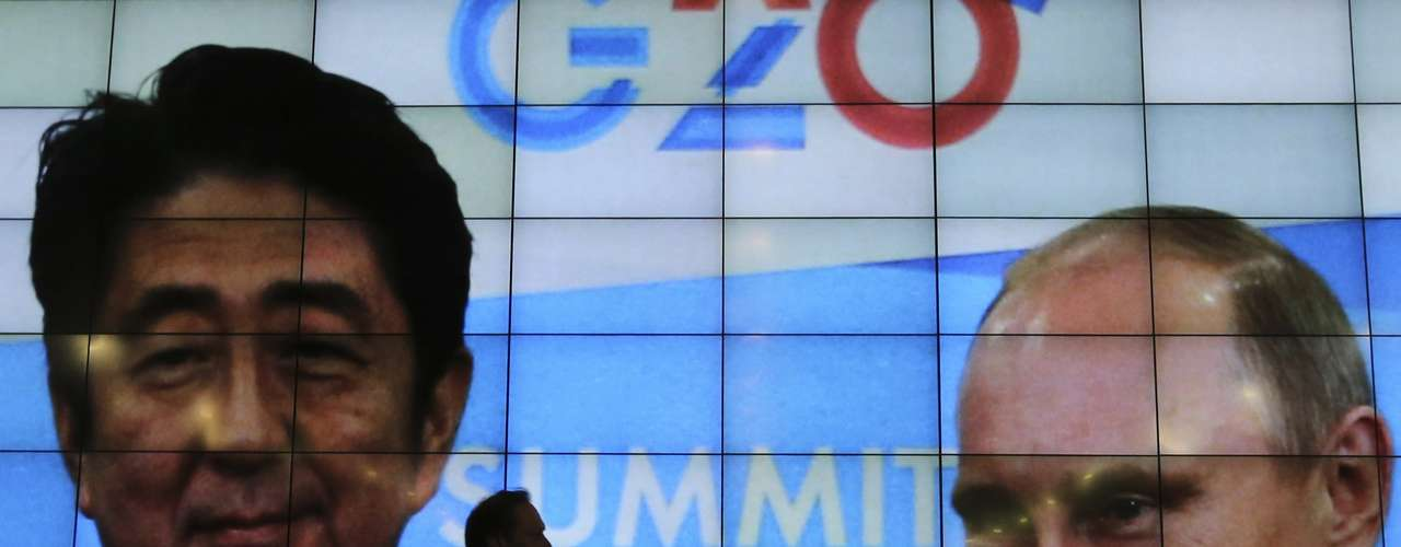 A man walks past a screen showing Russia's President Vladimir Putin (R) and Japan's Prime Minister Shinzo Abe at the press centre of the G20 summit in Strelna near St. Petersburg September 5, 2013. REUTERS/Alexander Demianchuk (RUSSIA - Tags: POLITICS BUSINESS)