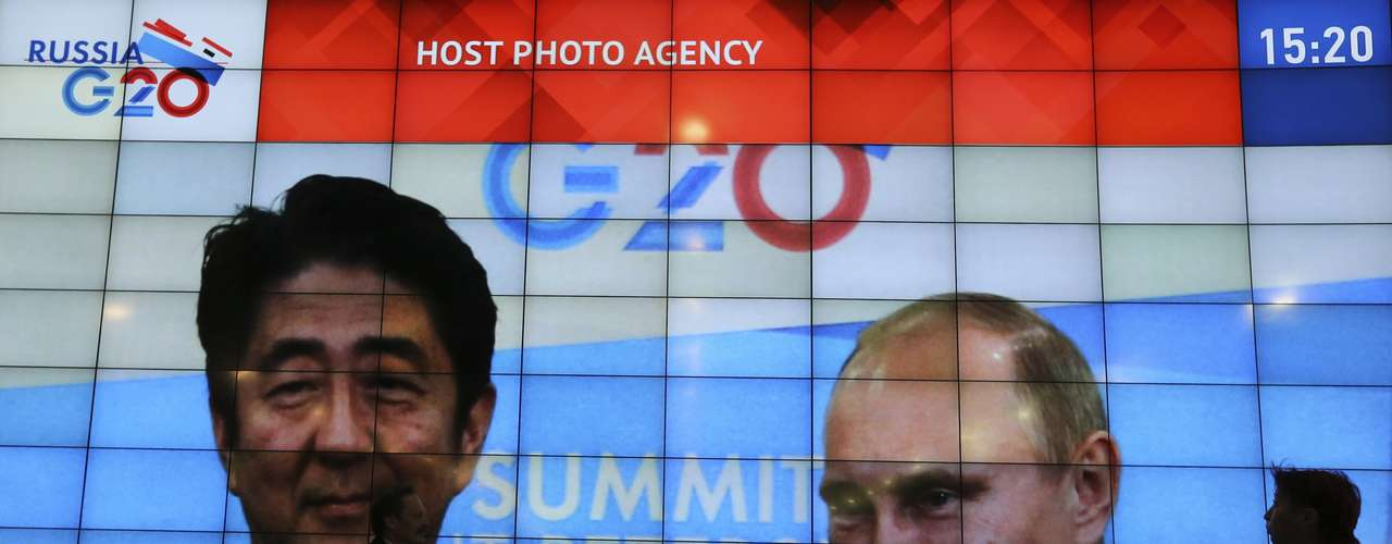 People walk past a screen showing Russia's President Vladimir Putin (R) and Japan's Prime Minister Shinzo Abe at the press centre of the G20 summit in Strelna near St. Petersburg September 5, 2013. REUTERS/Alexander Demianchuk (RUSSIA - Tags: POLITICS BUSINESS)