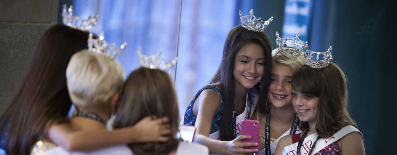 Miss America Nevada contestant supporters (L-R) Taryn Encinas, Lily Nelson and Karina Ferris take a photo in front of a mirror in the lobby before the preliminary round of the Miss America Pageant in Atlantic City, New Jersey, September 10, 2013. Miss America will be crowned during the final ceremony on Sunday, September 15.    REUTERS/Carlo Allegri  (UNITED STATES - Tags: ENTERTAINMENT SOCIETY)