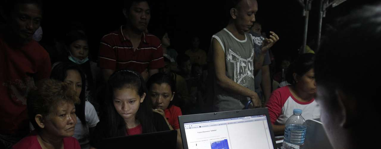Jessamere Enriquez, 14, helps her mother inform their family in Manila of their situation using Facebook at a free internet kiosk provided by an internet service provider after the Super typhoon Haiyan battered Tacloban city in central Philippines November 11, 2013. Due to the scarcity of resources, each person is allowed only 3 minutes of use. Dazed survivors begged for help and scavenged for food, water and medicine on Monday, as relief workers struggled to reach victims of a super typhoon that killed an estimated 10,000 people in the central Philippines. REUTERS/Edgar Su (PHILPPINES - Tags: DISASTER ENVIRONMENT)