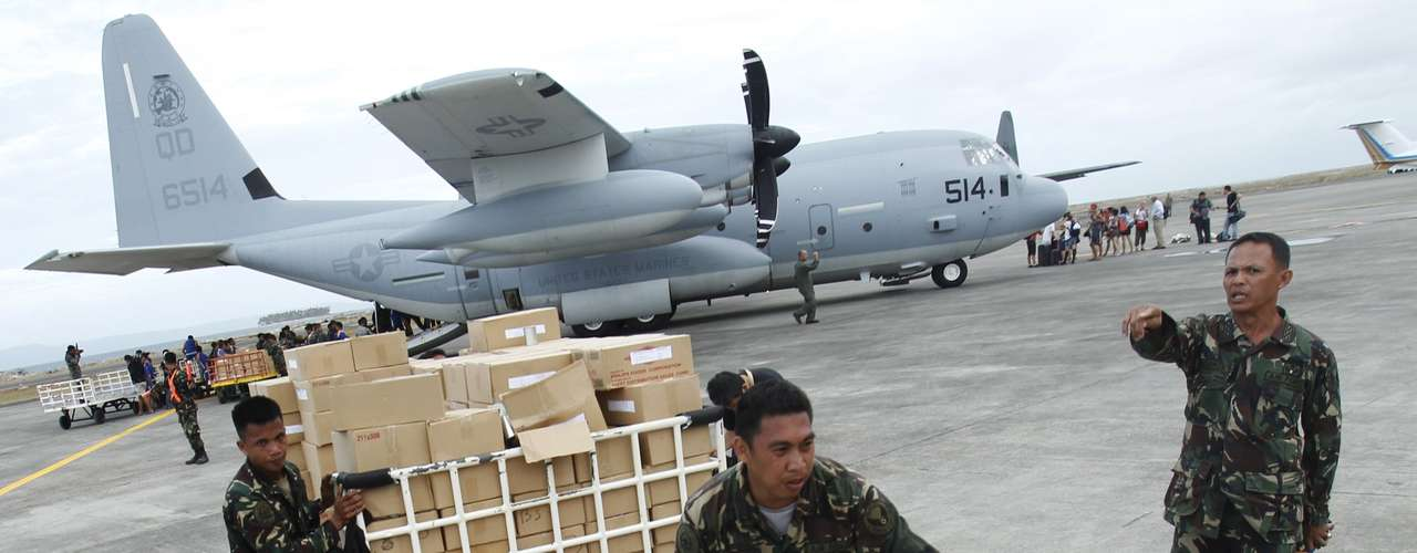 Military personnel deliver aid supplies at the destroyed airport after super typhoon Haiyan battered Tacloban City, in central Philippines November 11, 2013. Picture taken November 11, 2013. REUTERS/Edgar Su (PHILPPINES - Tags: DISASTER ENVIRONMENT MILITARY)