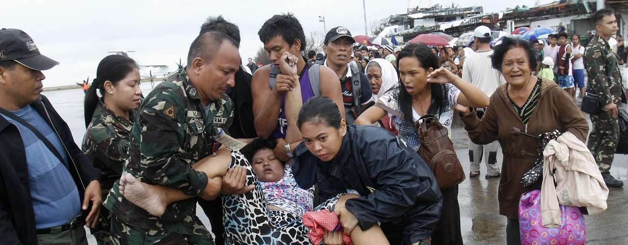 Military personnel carry a woman after she fainted while waiting in line to leave the town on military air transport, at the destroyed airport after super typhoon Haiyan battered Tacloban City, in central Philippines November 12, 2013. REUTERS/Edgar Su (PHILPPINES - Tags: DISASTER ENVIRONMENT SOCIETY MILITARY)