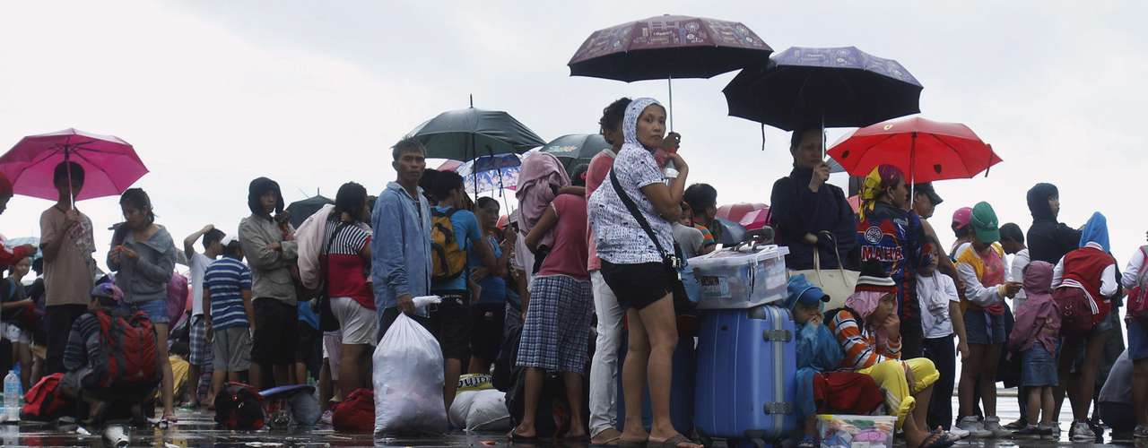 Residents who waited overnight for military transport to leave the town, stand in the rain as Philippines C-130 aircraft arrive, after super typhoon Haiyan battered Tacloban City  in central Philippines November 12, 2013. REUTERS/Edgar Su (PHILIPPINES - Tags: DISASTER ENVIRONMENT SOCIETY)
