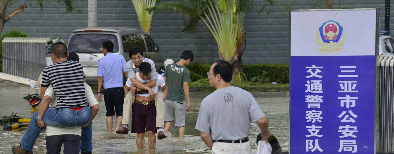 Residents wade through a flooded street outside a traffic police station after rainstorms triggered by Typhoon Haiyan hit Sanya, Hainan province November 11, 2013. Rainstorms from the typhoon hit the south China region on Sunday and Monday, killing at least four, with seven people still missing, according to Xinhua News Agency. Haiyan, one of the most powerful storms ever recorded, killed an estimated 10,000 people in central Philippines, according to officials. Picture taken November 11, 2013. REUTERS/China Daily (CHINA - Tags: ENVIRONMENT DISASTER SOCIETY CRIME LAW) CHINA OUT. NO COMMERCIAL OR EDITORIAL SALES IN CHINA