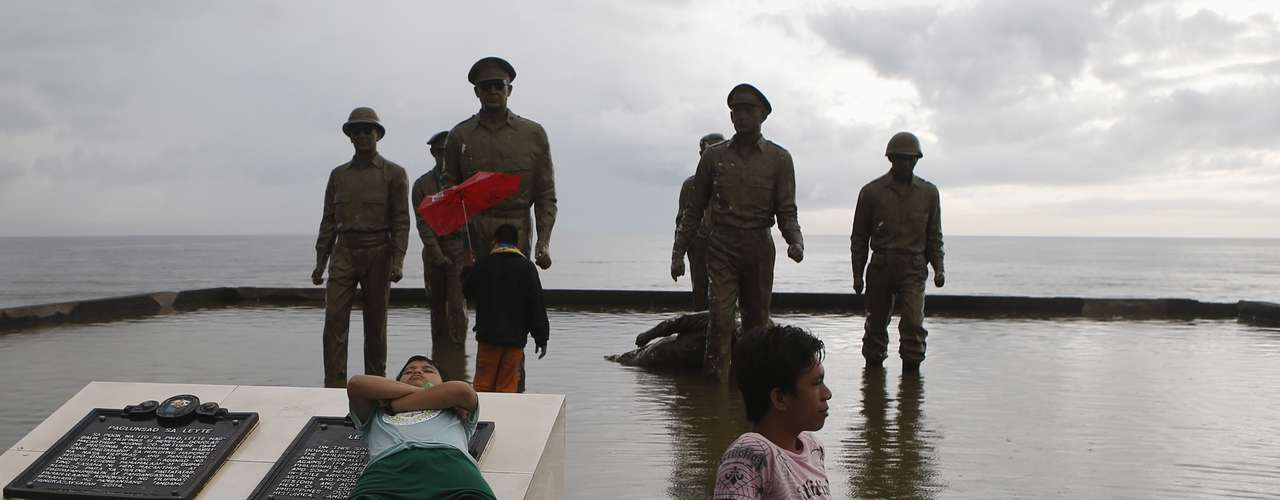 Survivors of super typhoon Haiyan rest in front of the U.S. General Douglas MacArthur shrine in Palo, Leyte province in central Philippines November 12, 2013. One of statues fell at the height of the typhoon last Friday, according to residents. REUTERS/Erik De Castro (PHILIPPINES - Tags: DISASTER ENVIRONMENT SOCIETY)