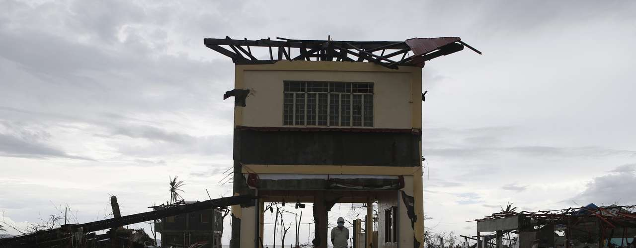 A man stands on the ground floor of his damaged house after super typhoon Haiyan battered Palo, Leyte province in central Philippines November 12, 2013. REUTERS/Erik De Castro (PHILIPPINES - Tags: DISASTER ENVIRONMENT)