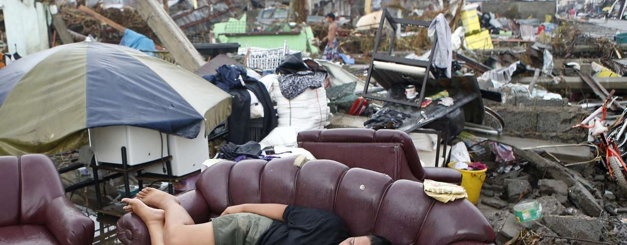 A typhoon victim rests on a sofa at the ruins of her family's home in Palo, Leyte province, which was battered by Typhoon Haiyan, in central Philippines November 12, 2013. Rescue workers tried to reach towns and villages in the central Philippines on Tuesday that were cut off by the powerful typhoon, fearing the estimated death toll of 10,000 could jump sharply, as relief efforts intensified with the help of U.S. military.   REUTERS/Erik De Castro (PHILIPPINES - Tags: DISASTER ENVIRONMENT)