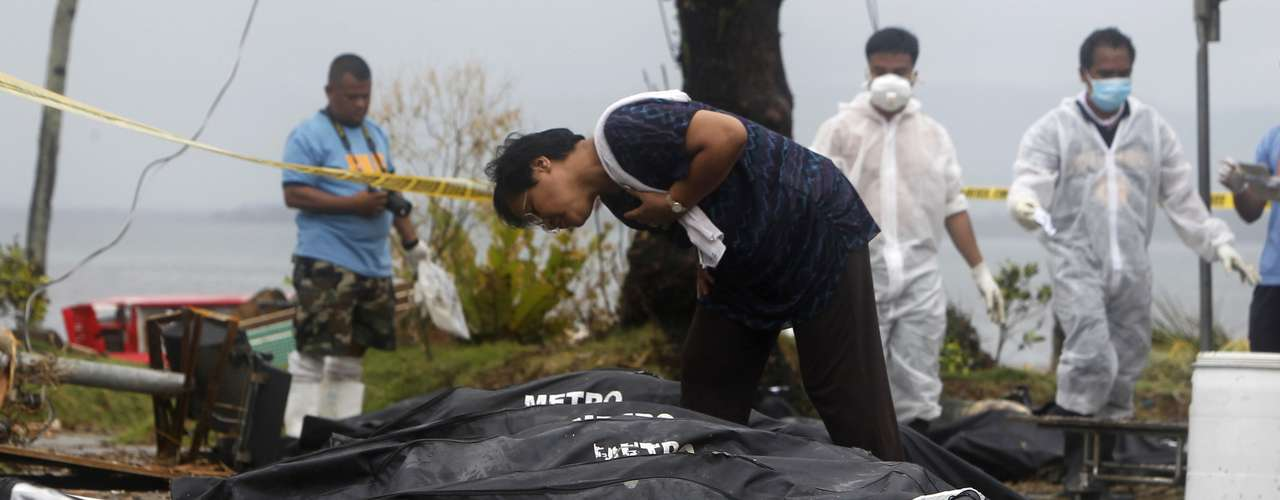 A woman searching for her missing loved ones looks at bags containing bodies of typhoon victims in Tacloban city, which was devastated by Typhoon Haiyan, in central Philippines November 12, 2013. Rescue workers tried to reach towns and villages in the central Philippines on Tuesday that were cut off by the powerful typhoon, fearing the estimated death toll of 10,000 could jump sharply, as relief efforts intensified with the help of U.S. military.   REUTERS/Romeo Ranoco (PHILIPPINES - Tags: DISASTER ENVIRONMENT)