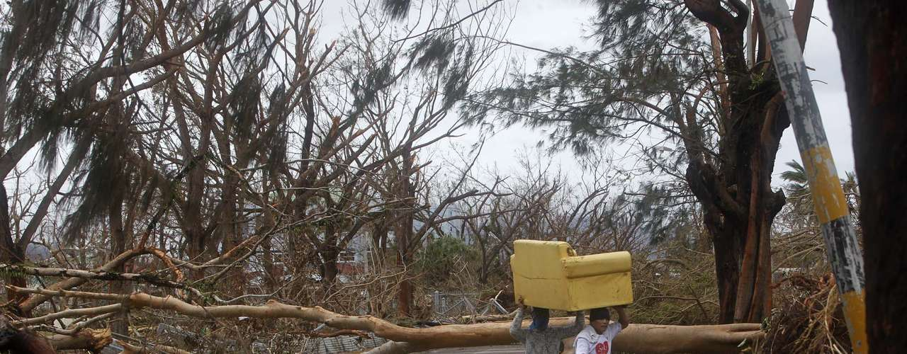 Residents carry a couch which they salvaged from their devastated home as they walk past uprooted and broken tree trunks after Typhoon Haiyan devastated Tacloban city, central Philippines November 12, 2013. Rescue workers tried to reach towns and villages in the central Philippines on Tuesday that were cut off by the powerful typhoon, fearing the estimated death toll of 10,000 could jump sharply, as relief efforts intensified with the help of U.S. military.    REUTERS/Romeo Ranoco (PHILIPPINES - Tags: DISASTER ENVIRONMENT)