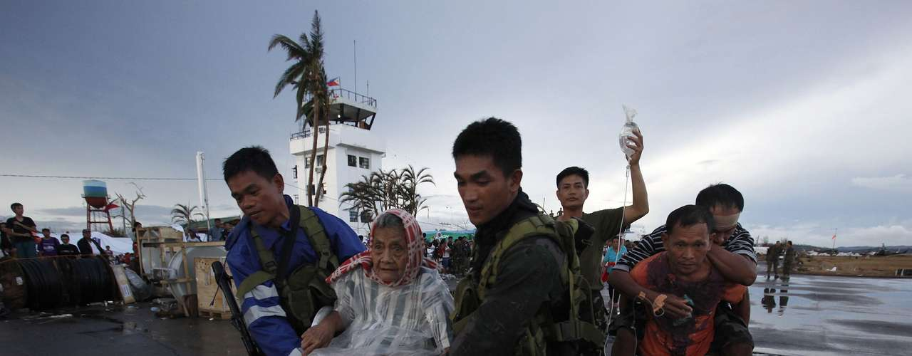 Filipino soldiers bring Tacloban residents onto a military plane leaving Tacloban airport in central Philippines November 12, 2013. Dazed survivors of super Typhoon Haiyan that swept through the central Philippines killing an estimated 10,000 people begged for help and scavenged for food, water and medicine on Tuesday, threatening to overwhelm military and rescue resources. REUTERS/Bobby Yip (CHINA - Tags: DISASTER ENVIRONMENT)
