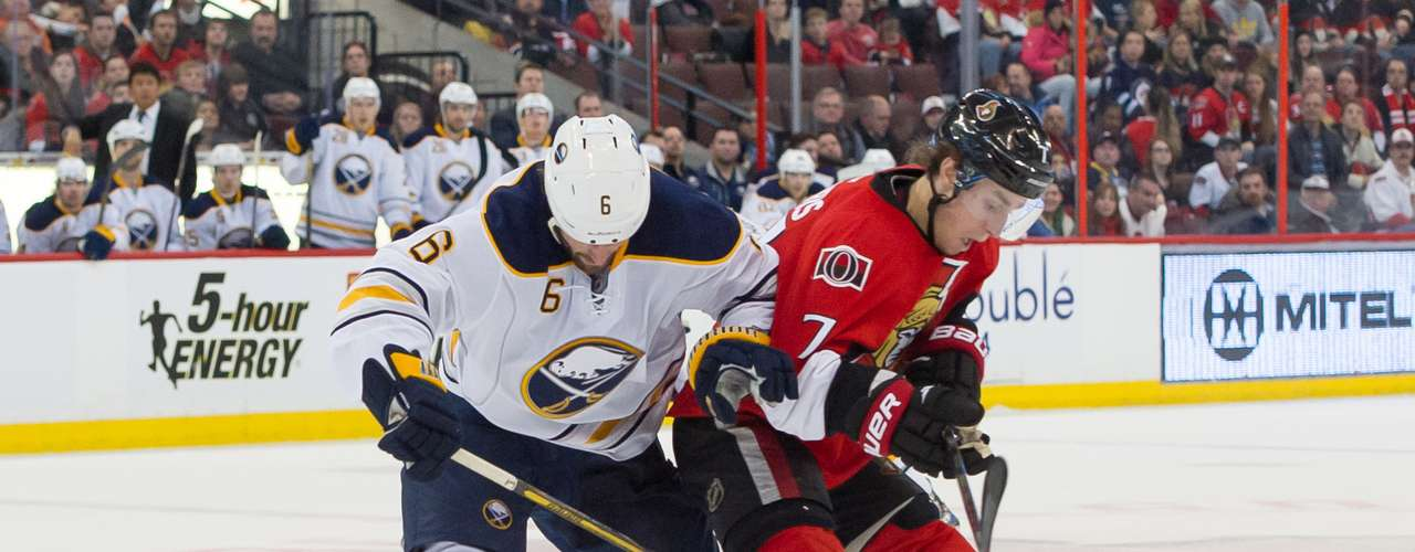 Dec 12, 2013; Ottawa, Ontario, CAN; Buffalo Sabres defenseman Mike Weber (6) and Ottawa Senators center Kyle Turris (7) battle for control of the puck in the second period at the Canadian Tire Centre. Mandatory Credit: Marc DesRosiers-USA TODAY Sports