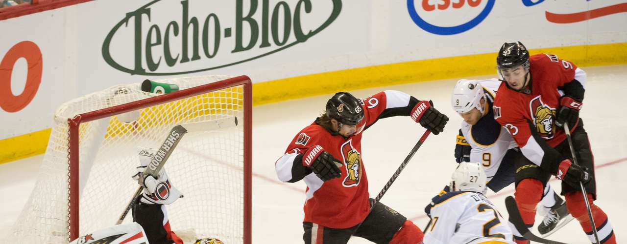 Dec 12, 2013; Ottawa, Ontario, CAN; Ottawa Senators defenseman Erik Karlsson (65) extends a leg to assit goalie Craig Anderson (41) in blocking a shot from Buffalo Sabres right wing Matt D'Agostinin (27) in the third period at the Canadian Tire Centre.The Senators defeated the Sabres 2-1. Mandatory Credit: Marc DesRosiers-USA TODAY Sports