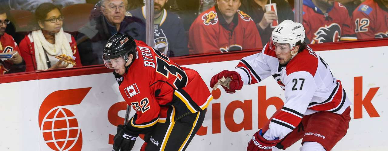 Dec 12, 2013; Calgary, Alberta, CAN; Calgary Flames center Paul Byron (32) skates with the puck as Carolina Hurricanes defenseman Justin Faulk (27) defends during the second period at Scotiabank Saddledome. Mandatory Credit: Sergei Belski-USA TODAY Sports