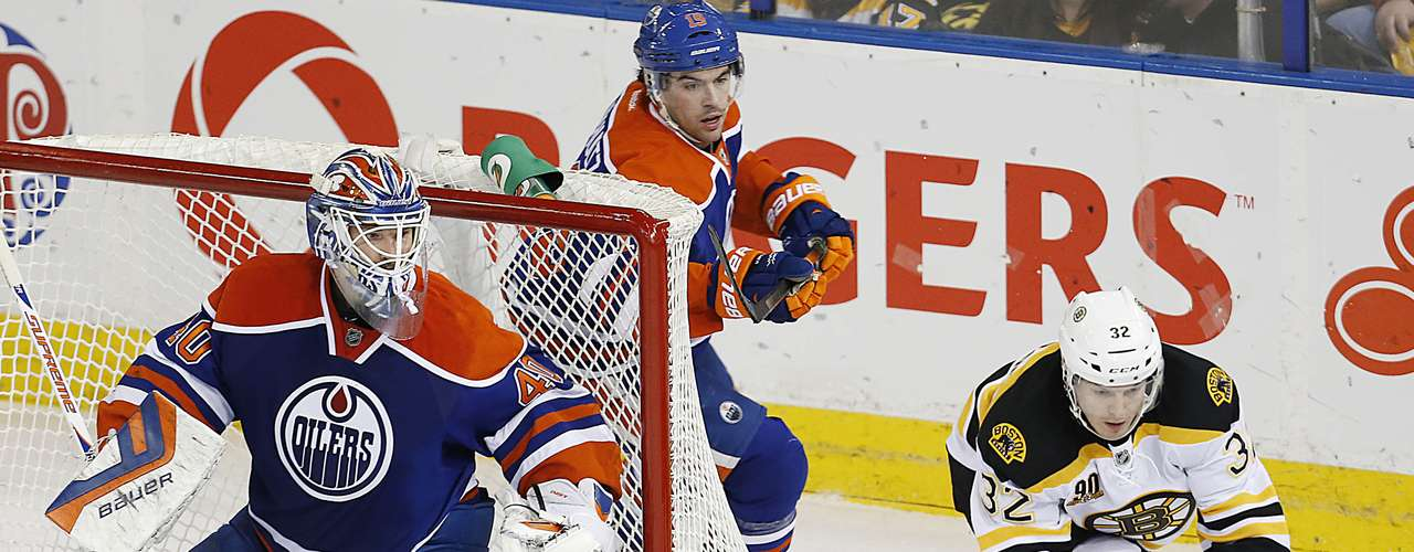Dec 12, 2013; Edmonton, Alberta, CAN; Boston Bruins forward Nick Johnson(32) reaches for a loose puck in front of Edmonton Oilers goaltender Devan Dubnyk (40) during the first period at Rexall Place. Mandatory Credit: Perry Nelson-USA TODAY Sports