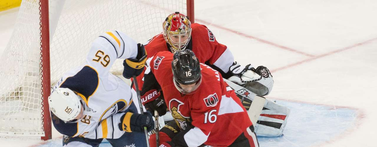 Dec 12, 2013; Ottawa, Ontario, CAN; Buffalo Sabres center Brian Flynn (65) and Ottawa Senators left wing Clarke MacArthur (16) battle for control of the puck in the third period at the Canadian Tire Centre.The Senators defeated the Sabres 2-1. Mandatory Credit: Marc DesRosiers-USA TODAY Sports