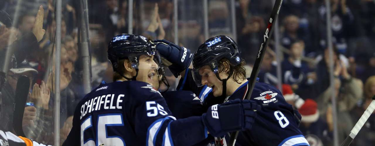 Dec 12, 2013; Winnipeg, Manitoba, CAN; Winnipeg Jets forward Blake Wheeler (26) celebrates his goal against the Colorado Avalanche with teammates during the third period at the MTS Center. Colorado wins 4-3 overtime. Mandatory Credit: Bruce Fedyck-USA TODAY Sports