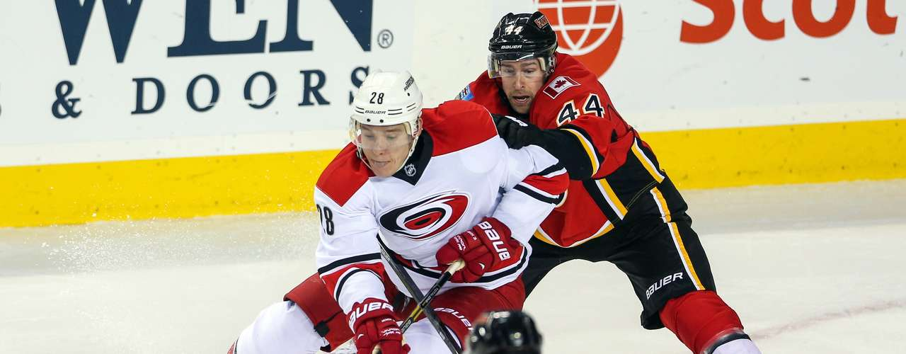 Dec 12, 2013; Calgary, Alberta, CAN; Carolina Hurricanes right wing Alexander Semin (28) and Calgary Flames defenseman Chris Butler (44) battle for the puck during the third period at Scotiabank Saddledome. Calgary Flames won 2-1. Mandatory Credit: Sergei Belski-USA TODAY Sports