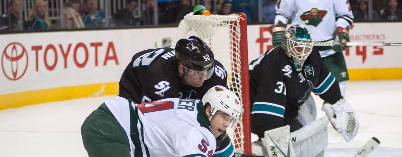 Dec 12, 2013; San Jose, CA, USA; Minnesota Wild forward Brett Bulmer (54) falls to the ice while attempting to control the puck against San Jose Sharks defenseman Matt Irwin (52) during the second period at SAP Center at San Jose. The San Jose Sharks defeated the Minnesota Wild 3-1. Mandatory Credit: Ed Szczepanski-USA TODAY Sports