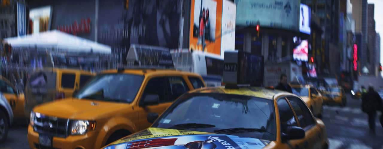 A reflection on a dark surface shows a taxi with a poster for the Super Bowl at Times Square as preparations continue for Super Bowl XLVIII in New York January 27, 2014.