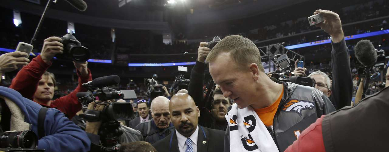 Denver Broncos quarterback Peyton Manning shakes a young boy's hand as he departs during Media Day.