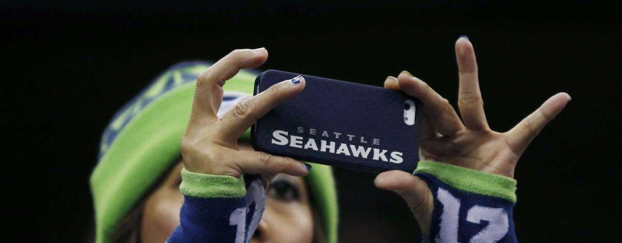 A Seattle Seahawks fan takes a picture from the stands as she attends Media Day for Super Bowl XLVIII at the Prudential Center in Newark, New Jersey January 28, 2014.