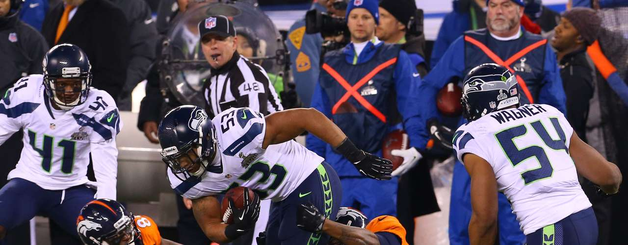 Seattle Seahawks outside linebacker Malcolm Smith (53), center, runs after recovering a fumble against the Denver Broncos in the third quarter in Super Bowl XLVIII.