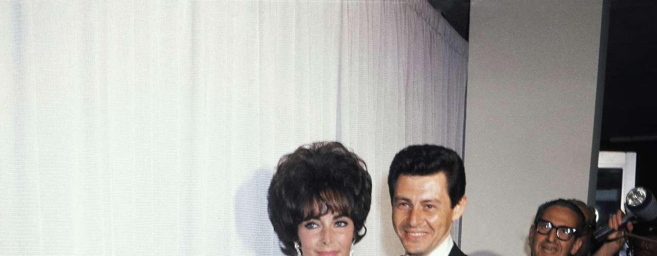 """La diva de las divas Elizabeth Taylor celebró su estatuilla en 1961 que recibió por su papel en """"Butterfield 8"""" con un vestido que se convirtió en un ícono de elegancia. Los guantes blancos y la boca roja dieron el toque final."""
