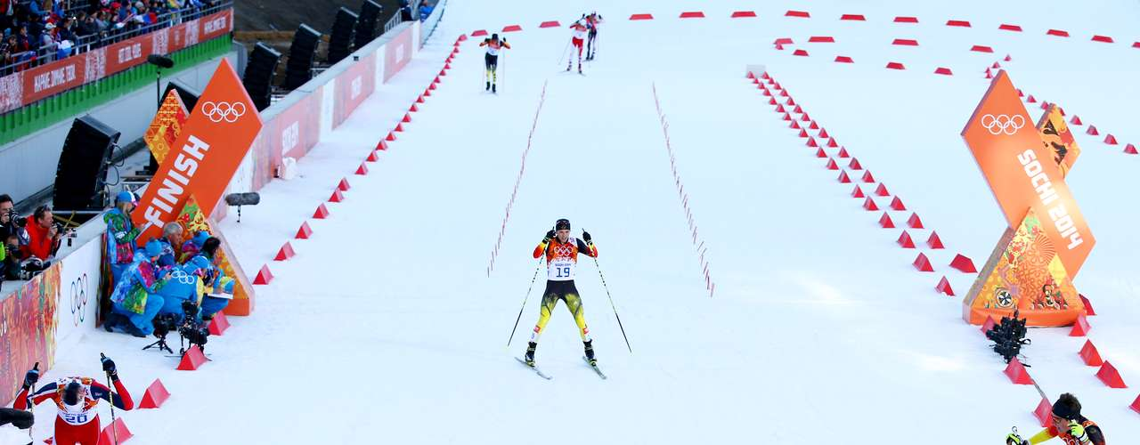 Eric Frenzel (2ndR) of Germany collapses with fellow competitors as he wins the gold medal during the Nordic Combined Individual