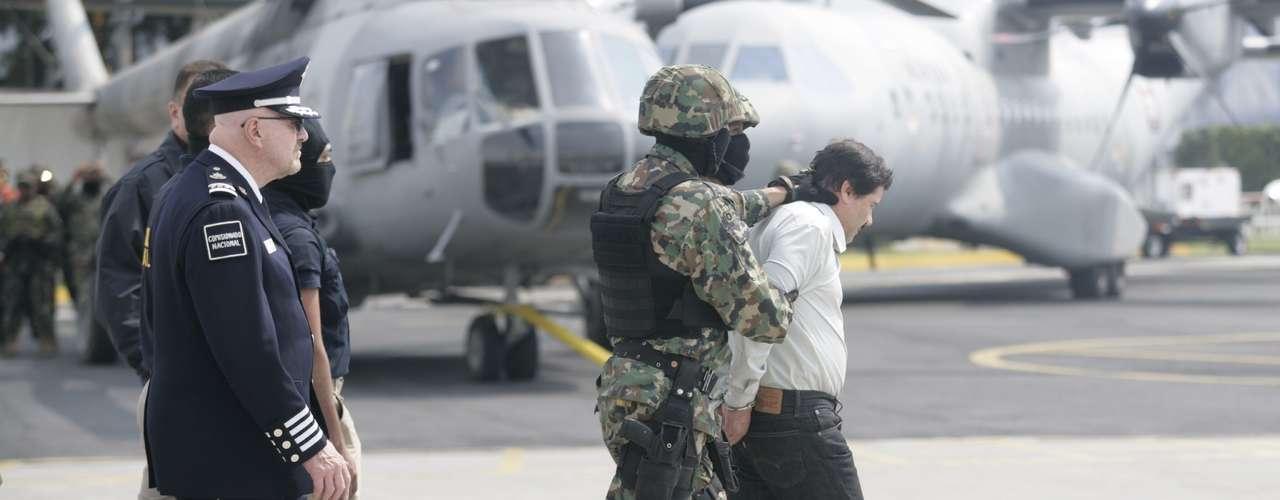 Ante las decenas de cámaras de video y fotografía, el capo fue conducido por elementos de la Marina y el comisionado nacional de Seguridad, Manuel Mondragón y Kalb, a un helicóptero federal.