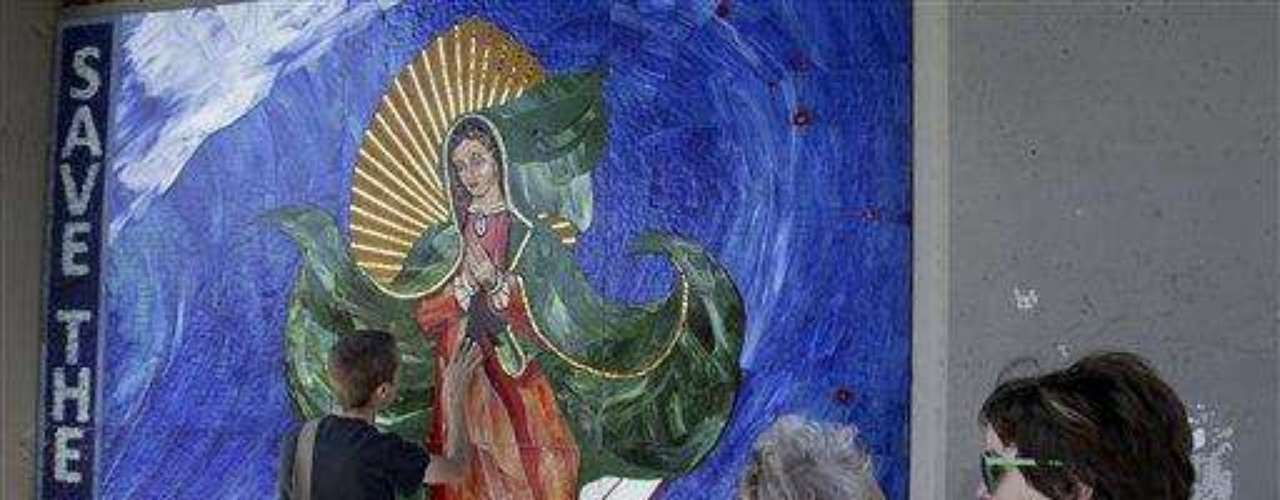 The surfing Madonna appeared just before Easter weekend and has been stirring a soulful debate in this Southern California beach town ever since.The striking mosaic of the Virgin of Guadalupe riding a wave was affixed to a wall under a train bridge by artists disguised as construction workers in April.It technically is graffiti that should be removed under the law.But the surfing Madonna's beauty is drawing a mass following and even city officials who say she must go acknowledge they too have been taken by her. They have spent thousands to hire an art conservation agency to find the best way to remove her without causing damage.The 10-by-10-foot rock and glass mosaic poses an interesting dilemma over whether a city should spend lots of money to get rid of artwork that is illegal but well done and actually beautifies a place.Deciding what is graffiti is a growing debate worldwide with guerrilla artists gaining respect in established art circles. A number of museums have brought t