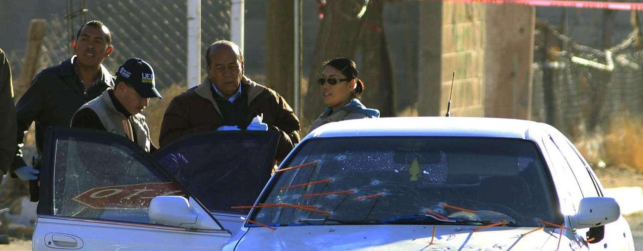 27-enero-2012.- Peritos forenses inspeccionan el vehículo donde la pareja de policías, Yadira Rodríguez y Adrián Herrera, fueron atacados cuando se desplazaban por una avenida del sureste de Ciudad Juárez. Los dos cuerpos sin vida de los policías quedaron dentro del automóvil en el que viajaban.