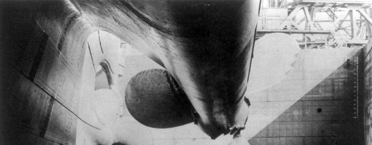 Obreros de pie junto a las propelas o hélices del RMS Titanic, en un astillero de Belfast, Irlanda del Norte, en una foto sin fecha.
