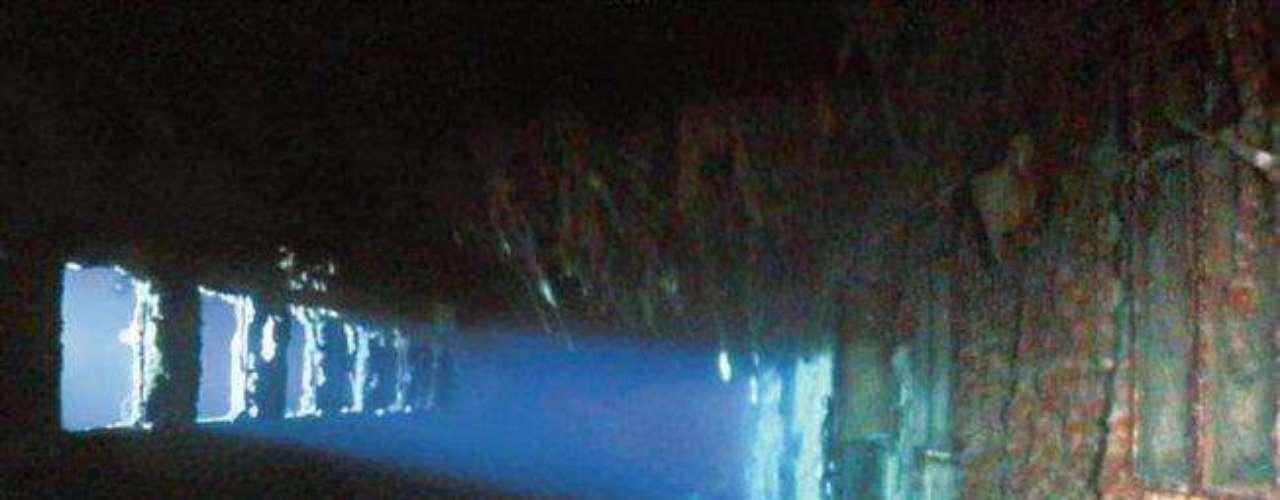 La cubierta de paseo: Las luces de un sumergible penetran en los oxidados restos de la cubierta de paseo de primera clase del Titanic, que en su día fue tan atractiva como esta del Olympic (foto siguiente). Antes del hundimiento del Titanic las ventanas fueron abiertas, probablemente para cargar los botes salvavidas. Por una de ellas sacó el millonario John Jacob Astor IV a su esposa de 18 años y la puso en el bote número 4. Él permaneció a bordo y murió.